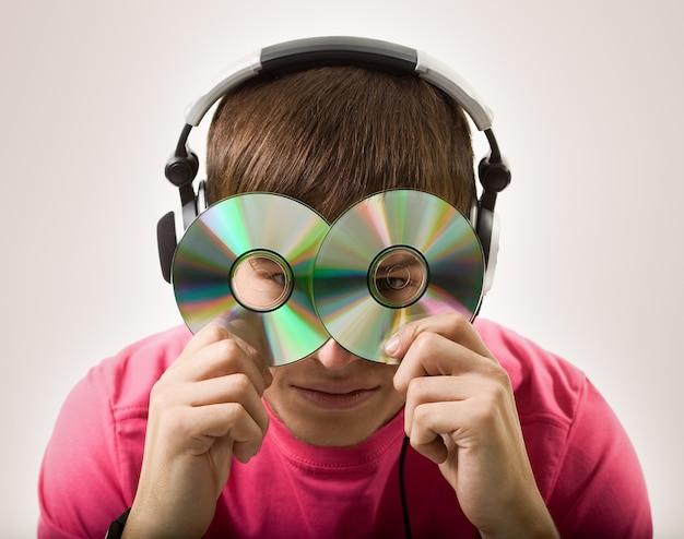 Portret van een onbekende jonge man in koptelefoon, twee cd's in zijn gezicht zetten