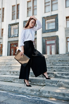 Portret van een onberispelijke jonge vrouw in witte blouse, wijde zwarte broek en klassieke hoge hakken poseren op de trap met zwarte laptop in haar hand met een enorm wit gebouw