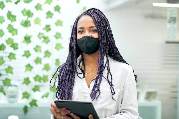 Portret van een onderneemster in het bureau die een tablet houdt die gezichtsmasker draagt