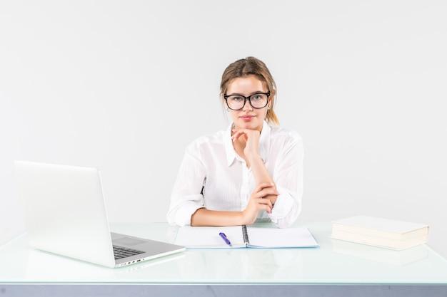 Portret van een onderneemsterzitting bij een bureau met laptop dat op witte achtergrond wordt geïsoleerd