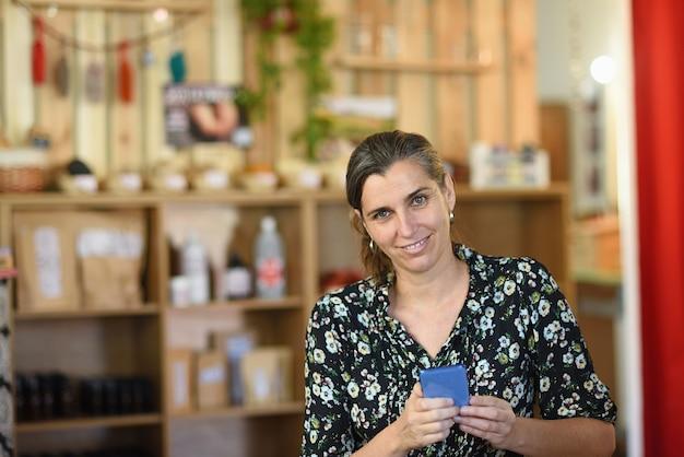 Portret van een ondernemende vrouw in haar winkel met haar mobiele telefoon
