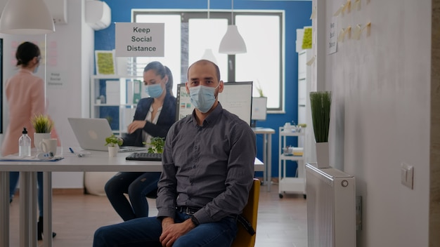 Portret van een ondernemer die een beschermend gezichtsmasker draagt tegen een pandemie van het coronavirus. werknemer die aan tafel in het kantoor werkt, houdt sociale afstand om virusziekte te voorkomen