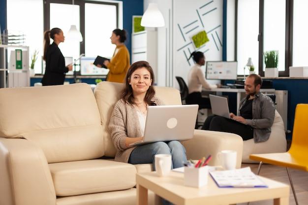 Portret van een ondernemer die op een laptop typt en naar de camera kijkt terwijl hij lacht terwijl een divers team op de achtergrond werkt