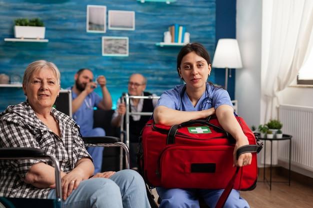 Portret van een ondersteunende verpleegster die een zak met een medicijnkit vasthoudt naast een gehandicapte senior patiënt