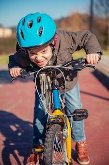 Portret van een ondeugende jongen met een uitdagend gebaar over zijn fiets, klaar om op een fietspad te rennen