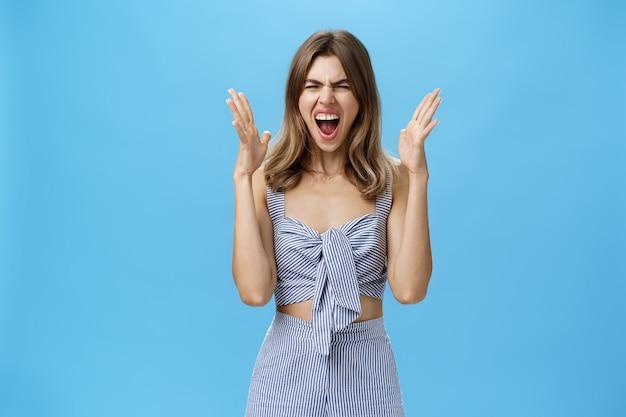 Portret van een ongelukkig onder druk gezette vriendin die schreeuwt van nood en instorting, schreeuwt, opgeheven handen schudt in de buurt van gezicht terwijl ruzie wordt gemaakt met een gevoel van hatelijk en woedend staan gehinderd over de blauwe muur. Premium Foto