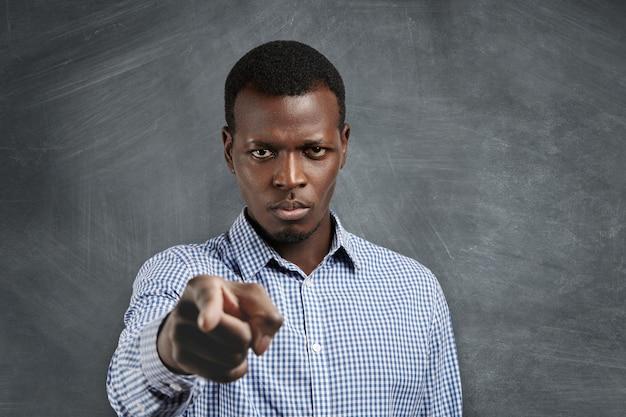 Portret van een ongelukkige afrikaanse baas met een gekke uitdrukking die met zijn wijsvinger wijst, boos kijkt en fronst alsof hij je beschuldigt of de schuld geeft voor fouten. selectieve aandacht op het gezicht van de man