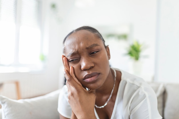 Portret van een ongelukkige afro-amerikaanse vrouw die thuis last heeft van kiespijn. gezondheidszorg, tandheelkundige gezondheid en probleemconcept. stock foto