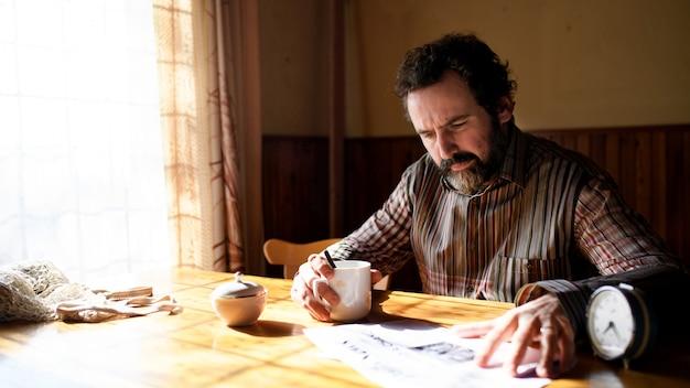 Portret van een ongelukkige arme volwassen man met koffie die thuis kranten leest, armoedeconcept