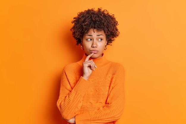 Portret van een ongelukkige, bedachtzame, melancholische jonge vrouw voelt zich boos kijkt opzij met een ontevreden uitdrukking denkt na over het oplossen van een probleem geïsoleerd over een oranje muur