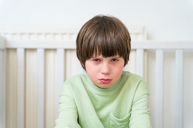 Portret van een ongelukkige en droevige jongen van tien jaar die alleen thuis zit.