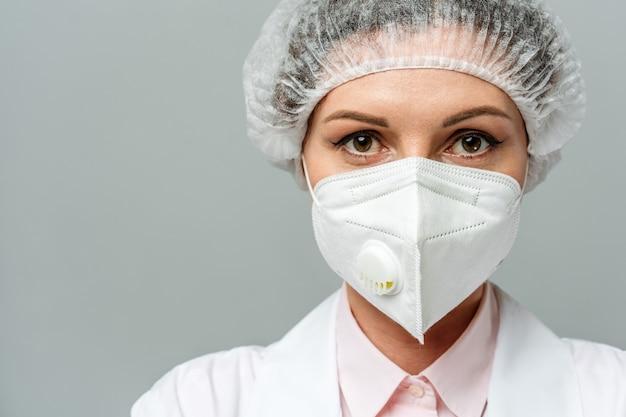 Portret van een ongelukkige jonge vrouwelijke arts met een medisch masker op een grijze achtergrond, de dokters moe