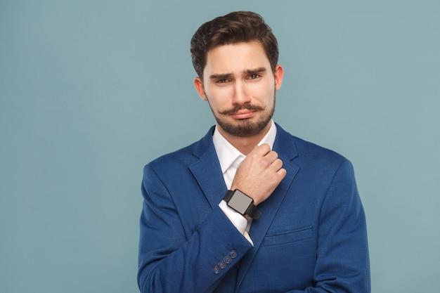 Portret van een ongelukkige zakenman met een klassiek jaket smart watch