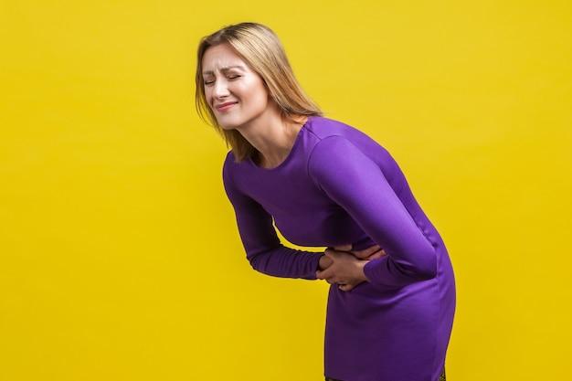 Portret van een ongezonde noodlijdende vrouw in een elegante paarse jurk die haar buik vasthoudt, grimassend van acute buikpijn, gastritis of constipatie. indoor studio-opname geïsoleerd op gele achtergrond
