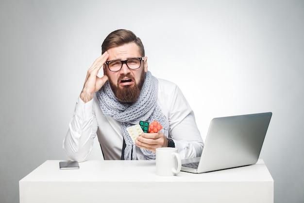 Portret van een ongezonde vermoeide jongeman in wit overhemd, sjaal en zwarte stropdas zit op kantoor en moet een belangrijk rapport afmaken, een grippe-virus hebben. studio opname, geïsoleerd, grijze achtergrond, binnen