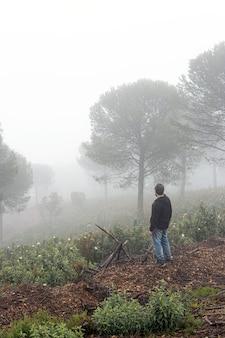 Portret van een onherkenbare man van achteren die op een mistige dag naar de horizon in het bos kijkt