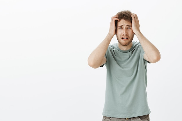 Portret van een onrustige, verwoeste jonge man die zijn baan verloor, de handen op het hoofd vasthield en fronste, zich bezorgd en angstig voelde bij het zien van een vreselijk ongeval