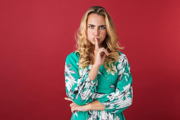 Portret van een ontevreden jonge mooie blonde schattige vrouw in jurk poseren geïsoleerd over rode muur met stilte gebaar