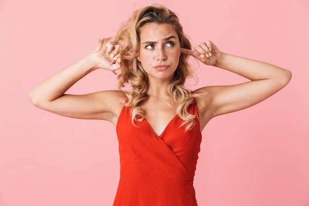 Portret van een ontevreden jonge mooie blonde schattige vrouw in jurk poseren geïsoleerd over roze muurbedekkende oren vanwege luide