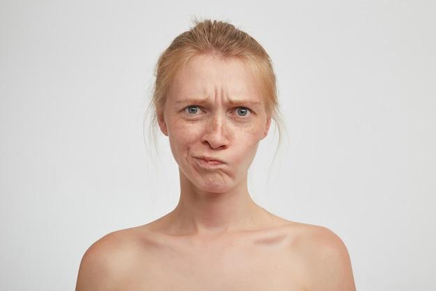 Portret van een ontevreden jonge roodharige vrouw die haar haar in de knoop draagt terwijl ze over een witte muur staat, met fronsende wenkbrauwen en een draaiende mond met een verbaasd gezicht