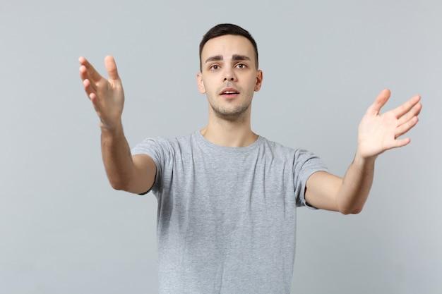 Portret van een ontevreden jongeman in vrijetijdskleding staat met uitgestrekte handen