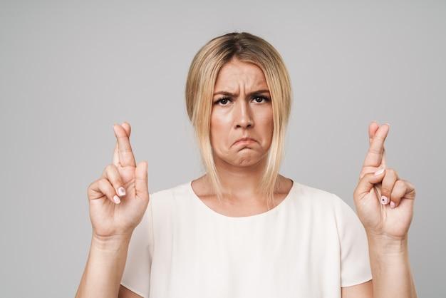 Portret van een ontevreden trieste mooie jonge blonde vrouw poseren geïsoleerd over grijze muur gekleed in basic wit t-shirt, maakt hoopvol gebaar met gekruiste vingers