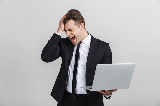 Portret van een ontevreden, verontwaardigde jonge zakenman in kantoorpak die schreeuwt terwijl hij zijn laptop geïsoleerd houdt