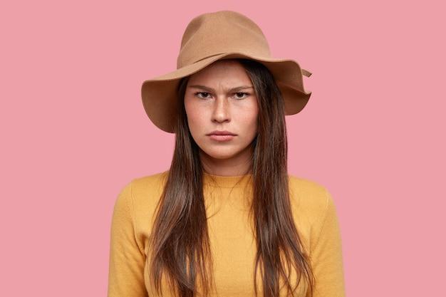 Portret van een ontevreden vrouw heeft een droevige, ongelukkige uitdrukking van ontevredenheid, een huid met sproeten, voelt zich ongelukkig