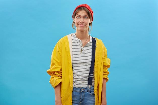 Portret van een ontevreden vrouw met een rode hoed, een gele regenjas en een overall die haar gezicht fronst en een slecht humeur heeft omdat haar man haar niet meenam op het meer om te gaan vissen. gezichtsuitdrukkingen en emoties
