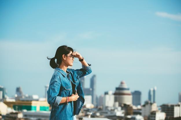 Portret van een ontspannen aziatische vrouw kijkt uit op de horizon stadsgezicht op de achtergrond