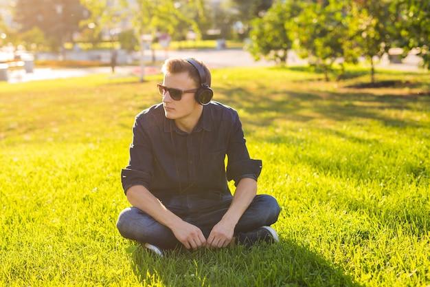 Portret van een ontspannen jonge man zittend op het gras in het park en luisteren naar muziek op een koptelefoon.