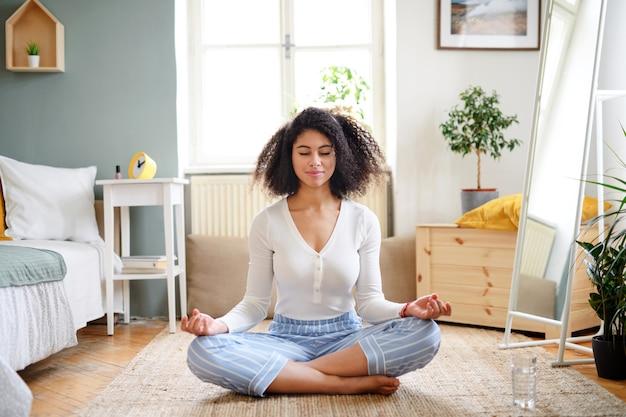 Portret van een ontspannen jonge vrouw binnenshuis, die yoga-oefening doet.