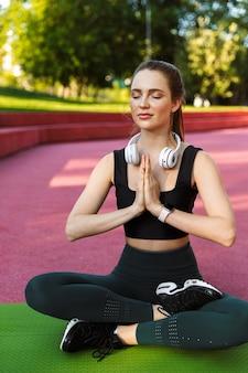 Portret van een ontspannen sportieve vrouw die een trainingspak draagt dat de handpalmen bij elkaar houdt en mediteert op een fitnessmat terwijl ze yoga beoefent in een groen park