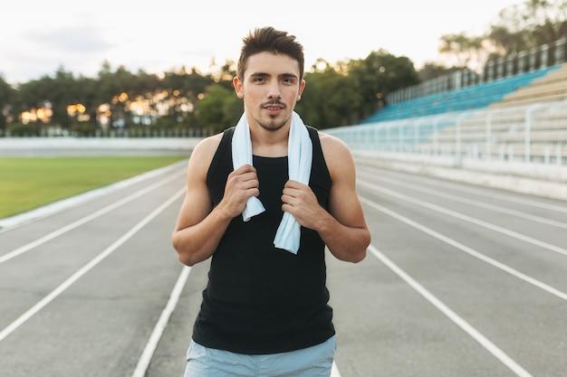 Portret van een ontspannende fitness man met handdoek op schouders