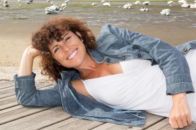 Portret van een ontspannende vrouw op het houten dek