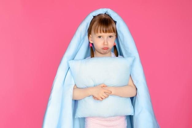 Portret van een ontstemd meisje van 5-6 jaar op een roze muur met een kussen en deken, het kind maakt zich op voor bed