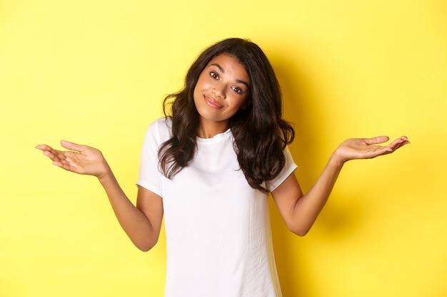 Portret van een onwetend, mooi afrikaans-amerikaans meisje, schouderophalend en glimlachend, verontschuldigend dat ze zich niet bewust was, staande over een gele achtergrond.