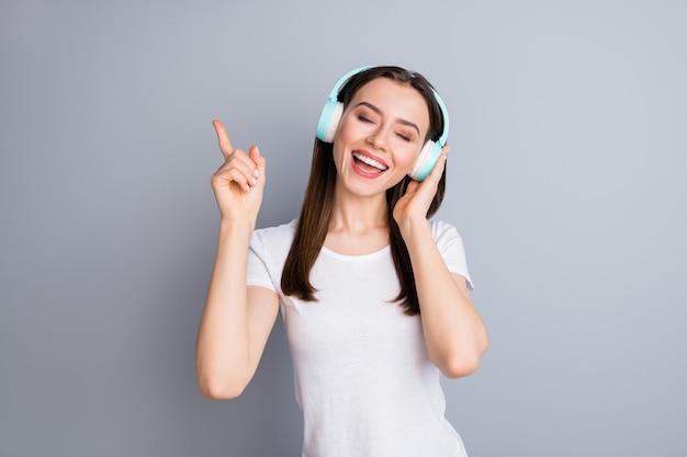 Portret van een openhartig enthousiast opgewonden meisje luistert naar discomuziek