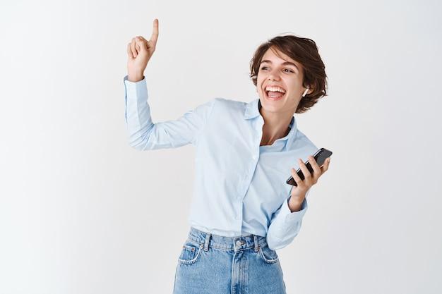 Portret van een openhartige gelukkige vrouw die danst, muziek luistert in een draadloze koptelefoon, de telefoon vasthoudt en omhoog wijst, witte muur