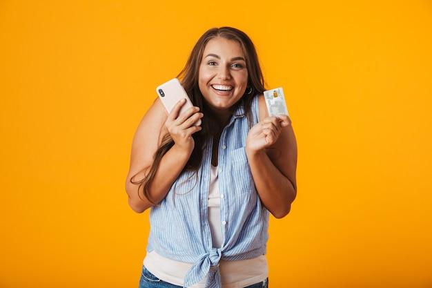 Portret van een opgetogen jonge casual vrouw, met plastic creditcard en mobiele telefoon