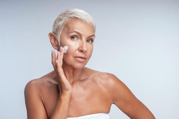 Portret van een opgetogen vrouw die voor de camera poseert terwijl ze voor haar huid zorgt