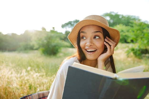 Portret van een opgetogen vrouw met een lippiercing en een strohoed die een boek leest terwijl ze op het gras in een groen park zit