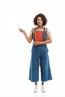 Portret van een opgetogen vrouw met een rugzak die met de vinger wijst naar copyspace en boeken vasthoudt die over een witte muur zijn geïsoleerd
