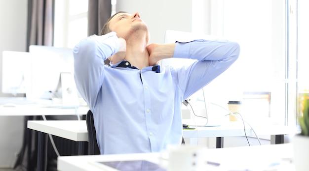 Portret van een opgetogen zakenman die ontspant in zijn kantoor