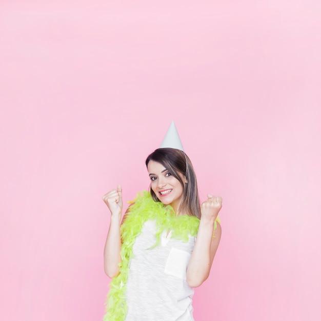 Portret van een opgewekte jonge vrouw op roze achtergrond