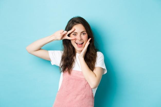 Portret van een opgewonden aantrekkelijke vrouw die een v-teken in de buurt van het oog toont, een kawaii-gebaar maakt en gelukkig glimlacht naar de camera, opgewekt tegen een blauwe achtergrond.