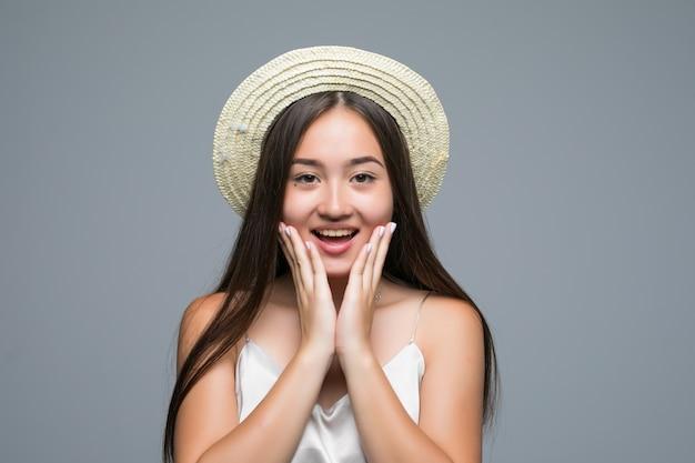 Portret van een opgewonden aziatische vrouw die camera over grijze achtergrond bekijkt