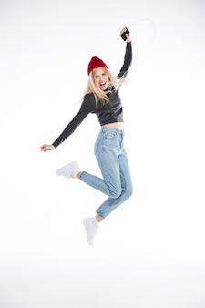 Portret van een opgewonden blonde jonge vrouw die in hoed met oortelefoons springt
