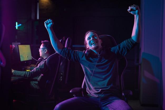 Portret van een opgewonden gamer zittend op een stoel en genietend van zijn overwinning in een computerspel