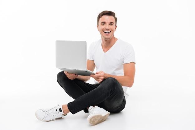 Portret van een opgewonden geamuseerde man die op laptop werkt